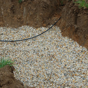 Gravel is filled into a recently excavated dry well