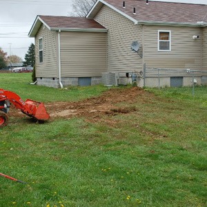 Excavator replaces soil on top of dry well next to a residential home