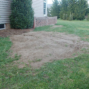 Excavation site for dry well next to a home
