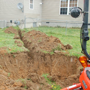 Experts installing a dry well and drainage system from a residential home